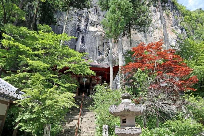 紅色觀音堂被樹木包圍著坐落於峭壁底端