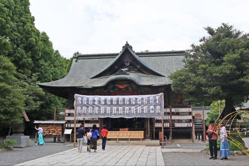 被大樹包圍著的秩父神社本殿前,及行走中的人群