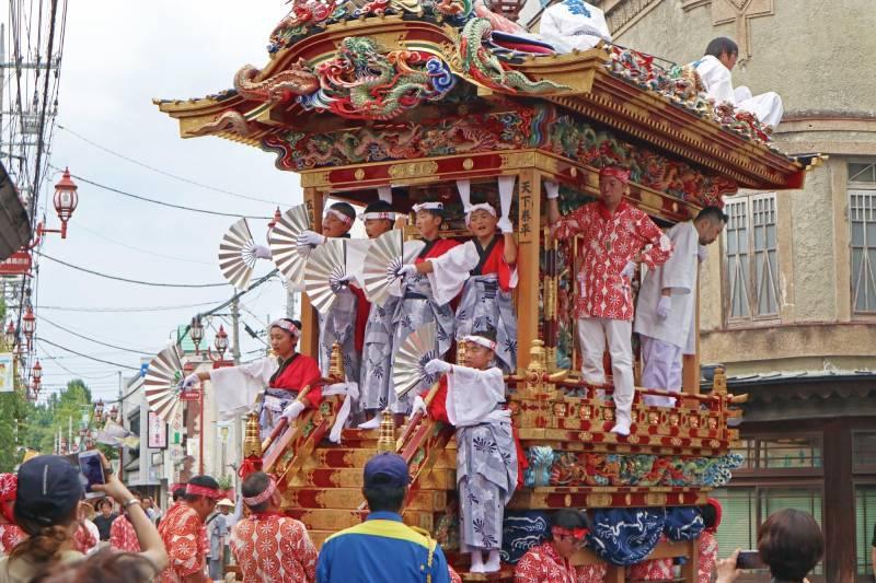 祭典上富麗的山車,山車上載著的孩子們手裡拿著裝飾扇子為祭典助陣