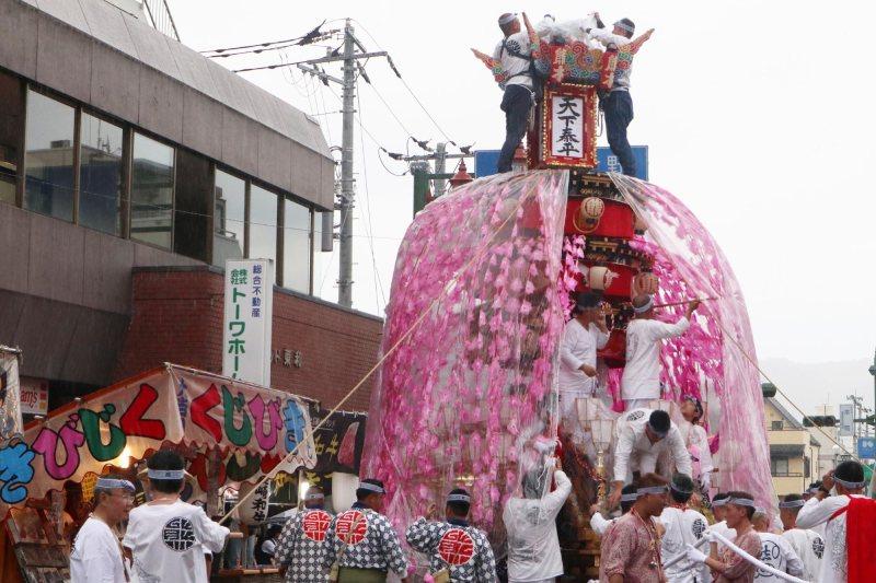 大雨中祭典依然進行著,人們正在為屋台穿上雨衣