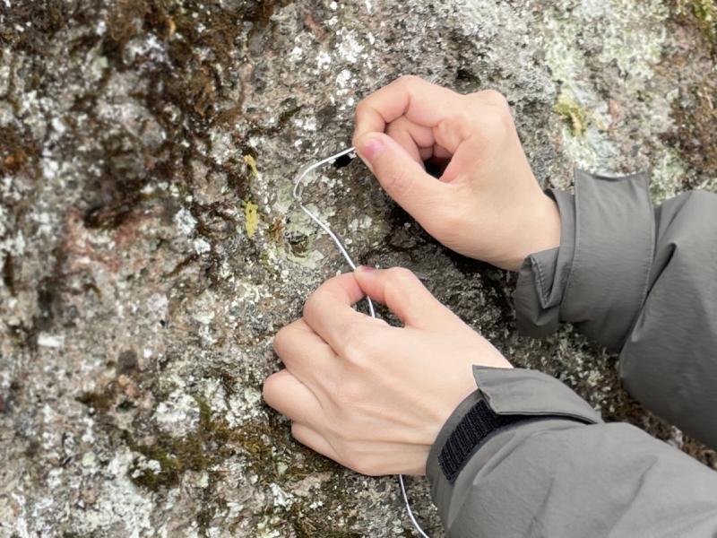 在岩石上用線穿過洞綁上五圓硬幣